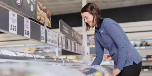 Työntekijä täyttää pakasteallasta myymälässä