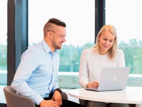 Työntekijät työskentelevät tietokoneen ääressä