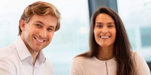 Kaksi työntekijää hymyilee kameralle