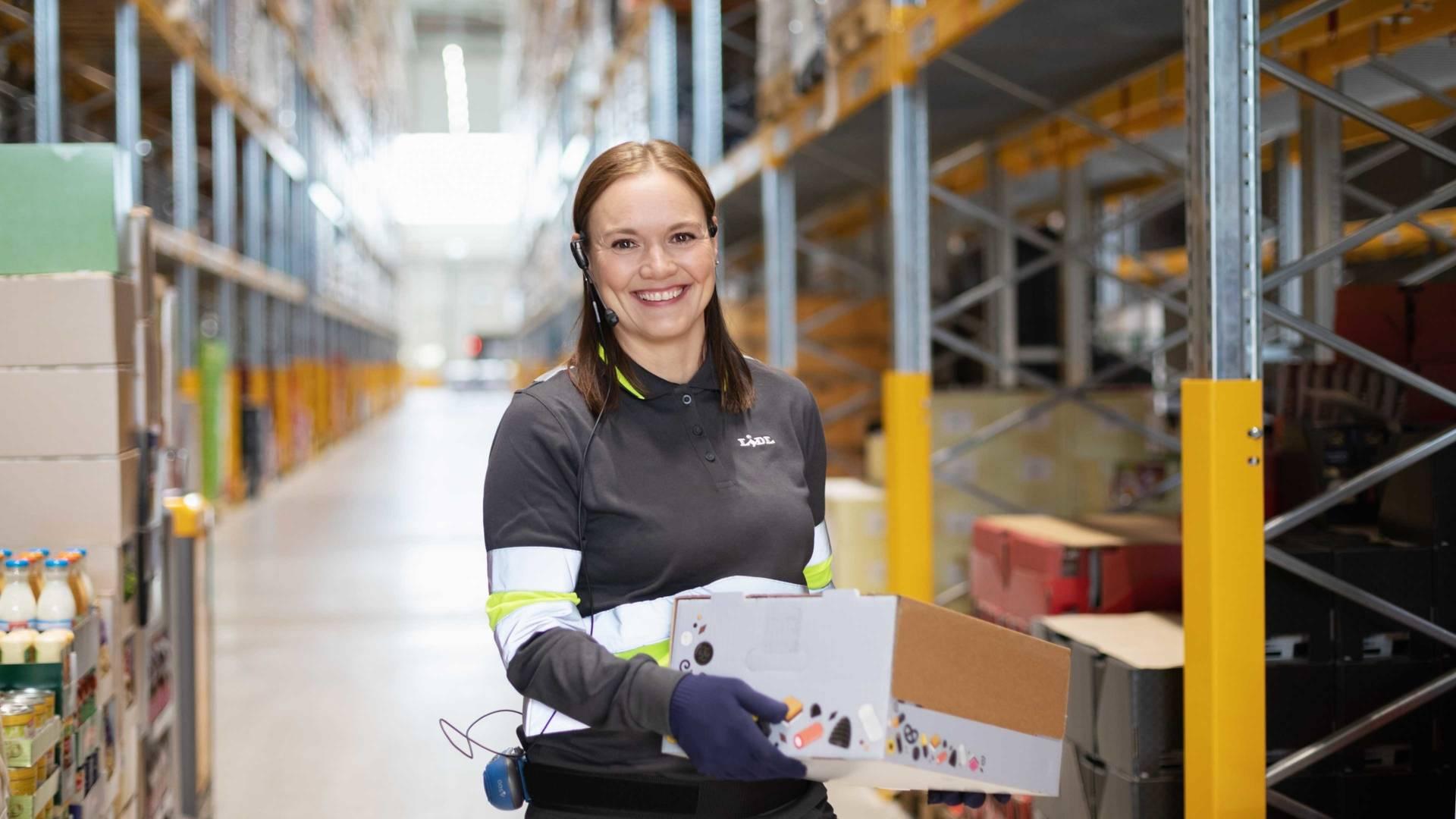 Työntekijä nostaa pakettia hymyillen