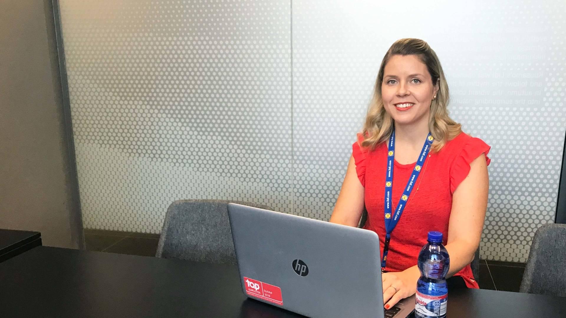 Nainen istuu neuvotteluhuoneessa työskennellen tietokoneella.